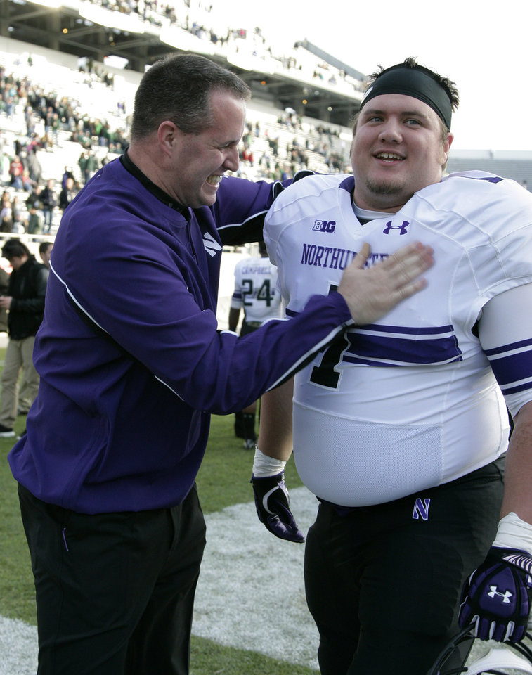 Photo -   Northwestern coach Pat Fitzgerald, left, celebrates with Bo Cisek following a 23-20 win over Michigan State in an NCAA college football game, Saturday, Nov. 17, 2012, in East Lansing, Mich. (AP Photo/Al Goldis)