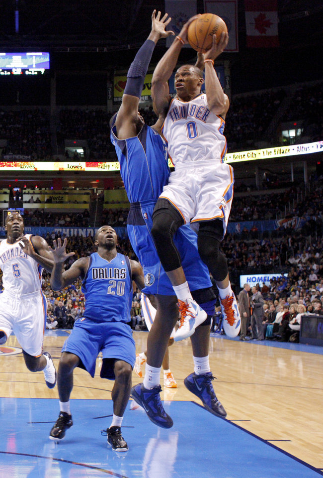 Photo - Oklahoma City's' Russell Westbrook (0) goes past Dallas' Brendan Haywood (33) during a preseason NBA game between the Oklahoma City Thunder and the Dallas Mavericks at Chesapeake Energy Arena in Oklahoma City, Tuesday, Dec. 20, 2011. Photo by Bryan Terry, The Oklahoman