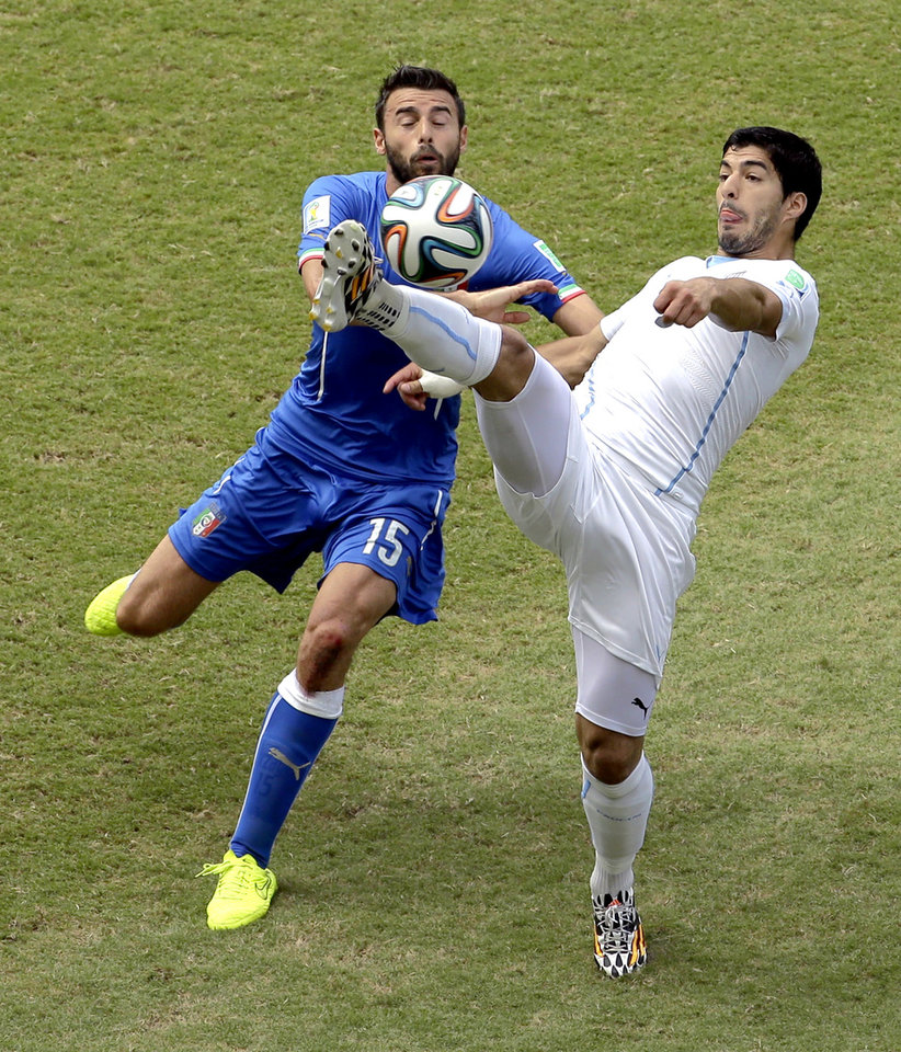 Photo - Uruguay's Luis Suarez, right, and Italy's Andrea Barzagli (15) challenge for the ball during the group D World Cup soccer match between Italy and Uruguay at the Arena das Dunas in Natal, Brazil, Tuesday, June 24, 2014. (AP Photo/Hassan Ammar)