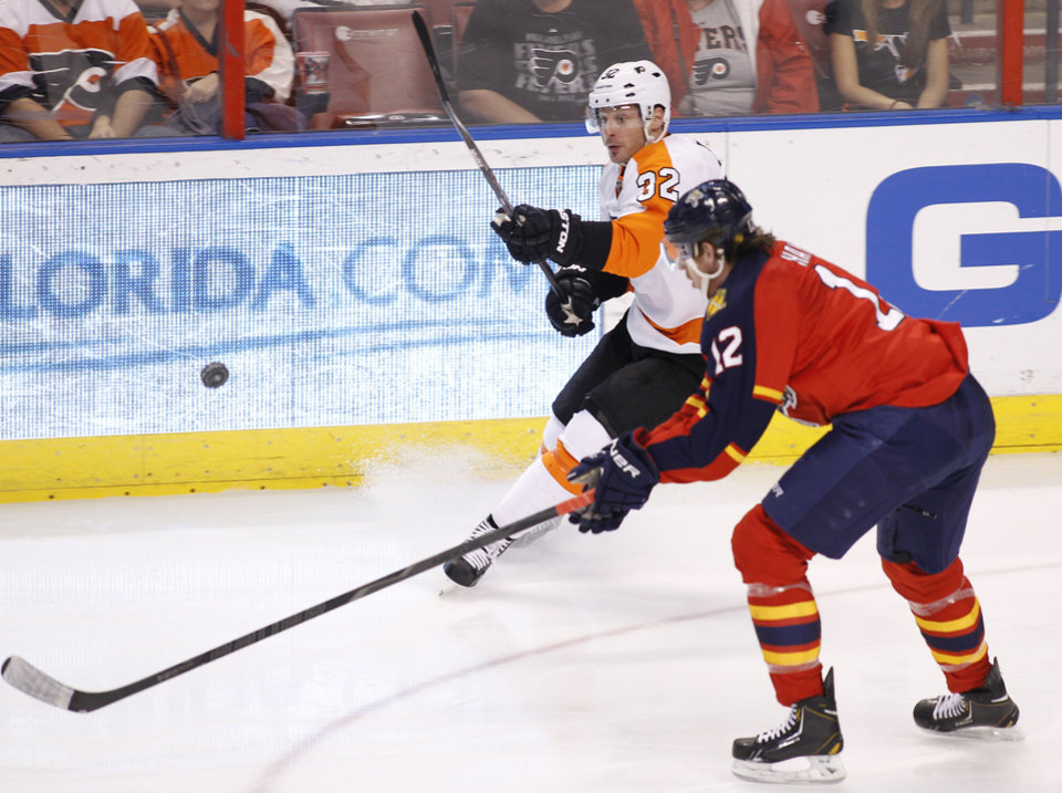 Photo - Philadelphia Flyers defenseman Mark Streit (32) and Florida Panthers right wing Jimmy Hayes (12) fight for the puck during the second period of an NHL hockey game in Sunrise, Fla., on Tuesday, April 8, 2014. (AP Photo/Terry Renna)