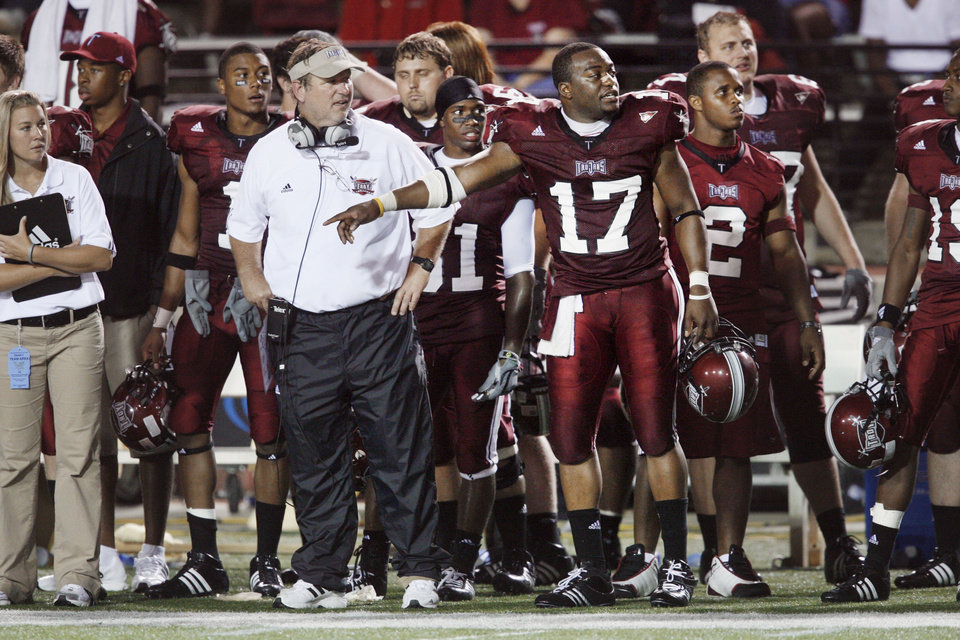 Photo - Head Coach Larry Blakeney and Omar Haugabook stand on the sidelines during the second half of their college football game between the Troy University Trojans and the Oklahoma State University Cowboys at Movie Gallery Veterans Stadium in Troy, Ala., Friday, September 14, 2007. BY STEVE SISNEY, THE OKLAHOMAN