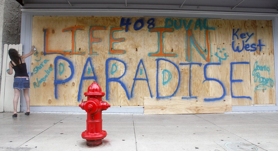 Shira Edllan Gervasi, of Israel, puts her name on plywood protecting a storefront in Key West, Fla., in anticipation of Tropical Storm Isaac on Saturday, Aug. 25, 2012.  Isaac's winds are expected to be felt in the Florida Keys by sunrise Sunday morning. (AP Photo/Alan Diaz) ORG XMIT: FLAD107