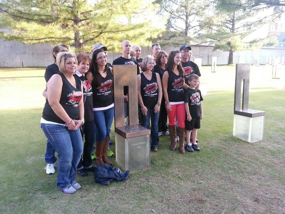 Photo -  Several runners from Stigler who participate in the Oklahoma City Memorial Marathon in memory of Stigler native Pamela Cleveland Argo pose for a photo around Pam's chair at the Memorial before the 2013 race. PHOTO PROVIDED    Photo by Ed Godfrey