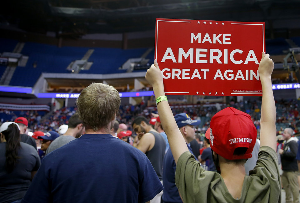 Photo - A support holds a sign before the President Donald Trump rally at the BOK Center in Tulsa, Okla., Saturday, June 20, 2020. [Sarah Phipps/The Oklahoman]