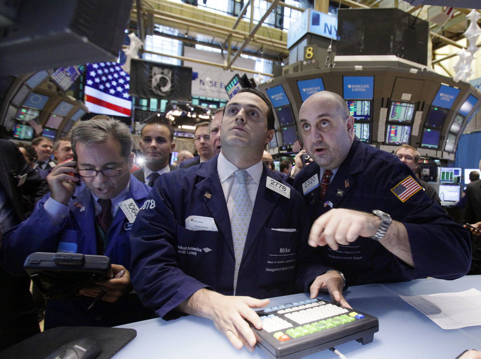 Specialists Michael Gagliano, center, and Peter Giacchi, right, work at their on the floor of the New York Stock Exchange during the IPO of Rose Rock Midstream, on Dec. 9, 2011. Rose Rock is a master limited partnership that controls the midstream assets of Tulsa-based SemGroup Corp. <strong>Richard Drew</strong>