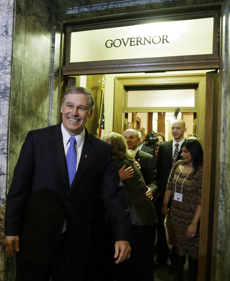 Gov. Jay Inslee, left, walks out of the Governor's office after paying a visit to former Gov. Chris Gregoire shortly after Inslee was sworn in, Wednesday, Jan. 16, 2013, in Olympia, Wash. (AP Photo/Ted S. Warren)