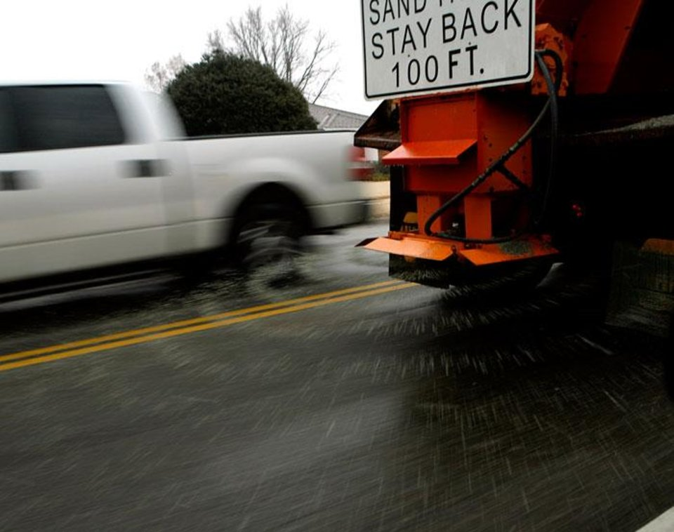 Photo -  A truck from the City of Edmond drops sand on 33rd street east of Boulevard during winter weather in Edmond, Okla., on Monday, Jan. 26, 2009. BY JOHN CLANTON, THE OKLAHOMAN