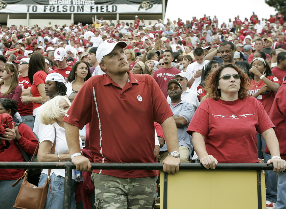 Photo - Shawn Browning, center, and Karen Sibley of Moore, OKla., watch after OU's loss to Colorado during the college football game between the University of Oklahoma Sooners (OU) and the University of Colorado Buffaloes (CU) at Folsom Field on Saturday, Sept. 28, 2007, in Boulder, Co.  By Bryan Terry, The Oklahoman