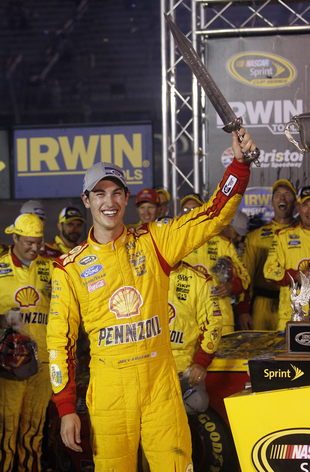 Photo - Joey Logano holds a sword presented to him after winning a NASCAR Sprint Cup Series auto race at Bristol Motor Speedway on Saturday, Aug. 23, 2014, in Bristol, Tenn. (AP Photo/Wade Payne)