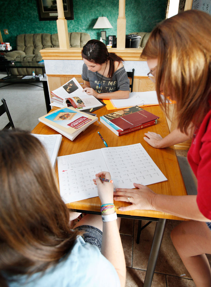 Johnni Dunford (right) works with her daughter Cassidy, 12,  while her other daughter Maddie, 17, studies her history during homeschooling class time at their home in Edmond, OK, Tuesday, Aug. 31, 2010. By Paul Hellstern, The Oklahoman