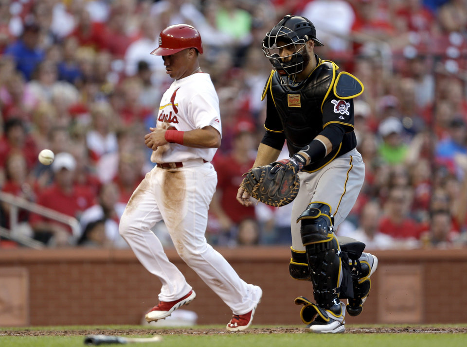 Photo - St. Louis Cardinals' Kolten Wong, left, scores on a sacrifice fly by Matt Carpenter as the throw gets away from Pittsburgh Pirates catcher Russell Martin during the third inning of a baseball game Thursday, July 10, 2014, in St. Louis. (AP Photo/Jeff Roberson)