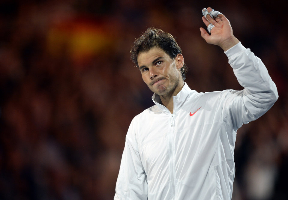 Photo - Rafael Nadal of Spain waves to the spectators during the trophy presentation after his loss to Stanislas Wawrinka of Switzerland in the men's singles final at the Australian Open tennis championship in Melbourne, Australia, Sunday, Jan. 26, 2014. (AP Photo/Andrew Brownbill)