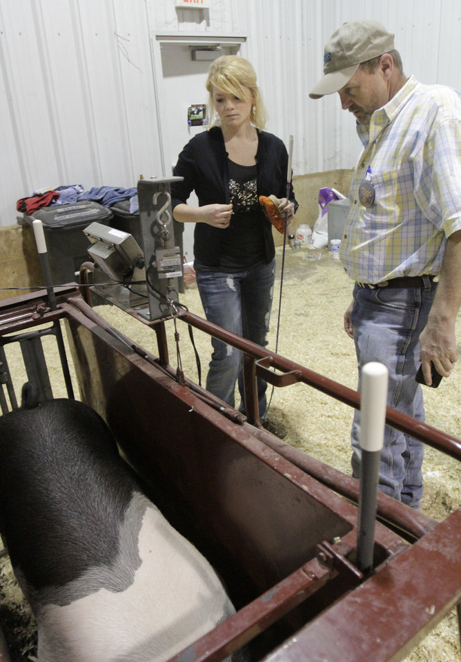 Yukon student Kaylen Baker and her agriculture teacher Tim Herren work with �Grandpa� during the Oklahoma Youth Expo at State Fair Park in Oklahoma City in March of 2012. <cutline_credit_leadin>Photo by Paul Hellstern, The Oklahoman Archive</cutline_credit_leadin> <strong>PAUL HELLSTERN</strong>