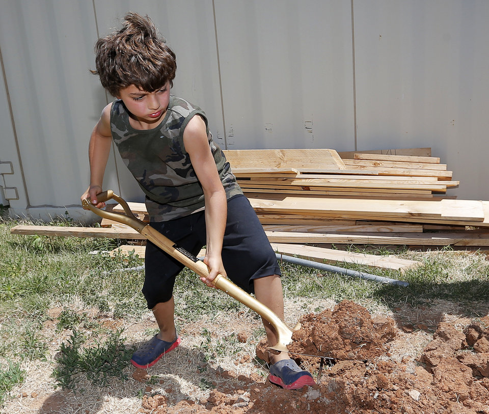 Photo -  Jacob Cohen, 9, shovels dirt as youths and parents from the Inter-Congregational Sunday School of Temple B'nai Israel and Emanuel Synagogue plant 10 trees on Oklahoma City property damaged by the May 20, 2013 tornado. Photo by Nate Billings, The Oklahoman   NATE BILLINGS -