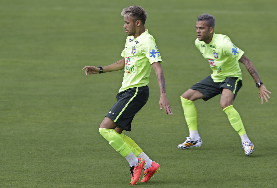 Photo - Brazil's Neymar, left, and Dani Alves practice during a training session of the Brazilian national soccer team at the Granja Comary training center in Teresopolis, Brazil, Sunday, June 15, 2014. Brazil plays in group A of the 2014 soccer World Cup. (AP Photo/Andre Penner)
