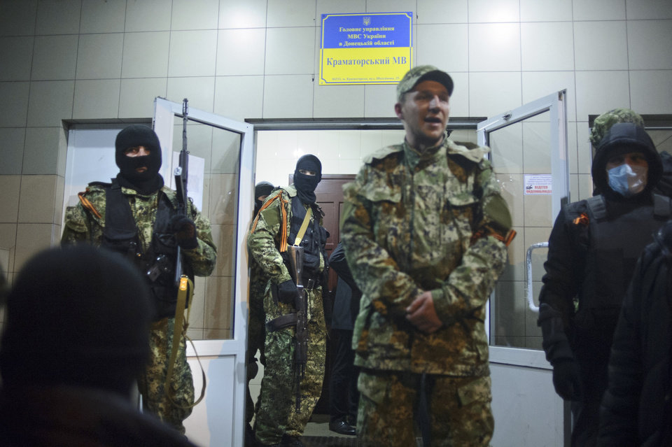 Photo - In this photo taken on Saturday, April  12, 2014, Armed pro-Russian activists stand outside the police station in the eastern Ukraine town of Kramatorsk. The interior minister overnight reported an attack on a police in the city of Kramatorsk, close to the city of Slovyansk. A video from local news web-site Kramatorsk.info showed a group of camouflaged men armed with automatic weapons storming the building. The news web-site also reported that supporters of the separatist Donetsk People's Republic have occupied the administration building, built a barricade with tires around it and put a Russian flag nearby.  (AP Photo/Maxim Dondyuk, Russian Reporter magazine) MAGAZINES OUT
