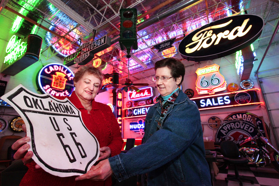 Kathy Anderson and Arlita Harris discuss a potential billboard and sign museum project Thursday. The signs are in a private collection but represent the type they would like to display in a proposed museum in Bethany. Photo By David McDaniel, The Oklahoman