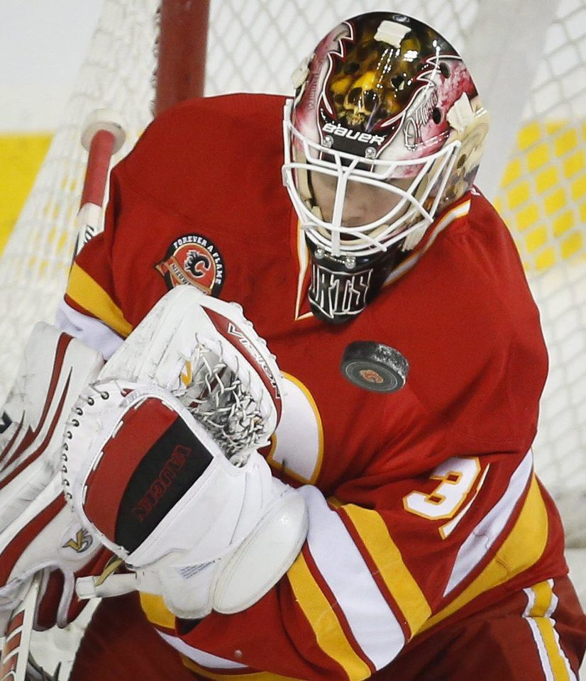 Photo - Calgary Flames goalie Joni Ortio, from Finland, bobbles the puck during the first period of an NHL hockey game against the New York Islanders on Friday, March 7, 2014, in Calgary, Alberta. (AP Photo/The Canadian Press, Jeff McIntosh)