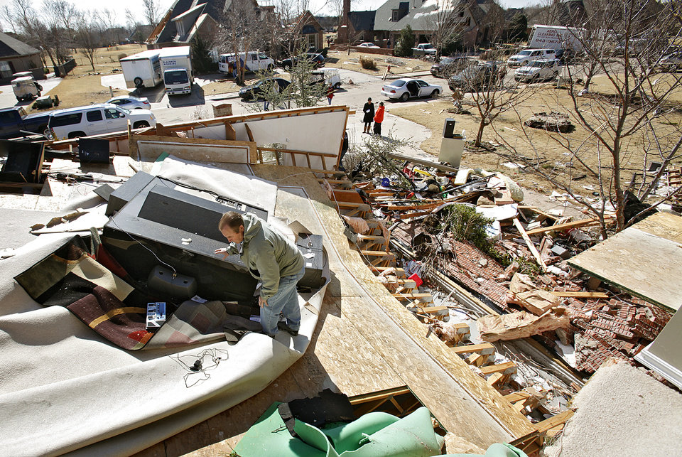 Photo - Craig Blakenship looks for salvageable items in what used to be his second story media room on Wednesday, Feb. 11, 2009, after his home was destroyed by a tornado on Tuesday in Edmond, Okla.  PHOTO BY CHRIS LANDSBERGER, THE OKLAHOMAN