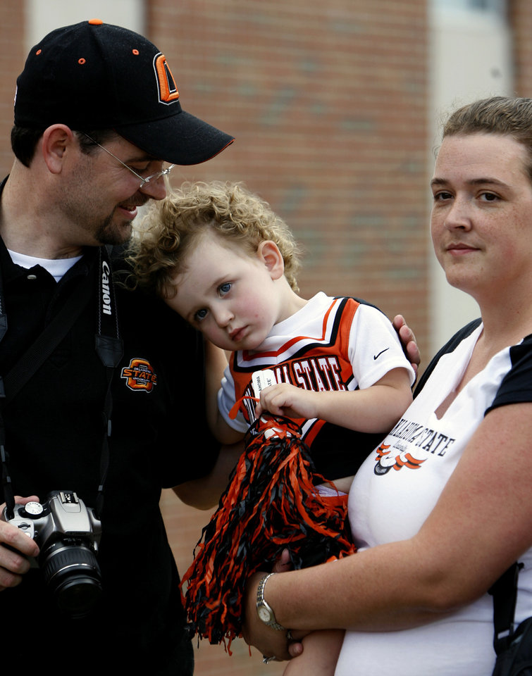 FANS, MIKE RAY, AMY RAY: Emma Ray, 2, is held by her parents Mike and Amy, from Maryville, Tenn., during a pep rally before the college football game between the Troy University Trojans and the Oklahoma State University Cowboys at Movie Gallery Veterans Stadium in Troy, Ala., Friday, September 14, 2007. BY MATT STRASEN, THE OKLAHOMAN ORG XMIT: KOD