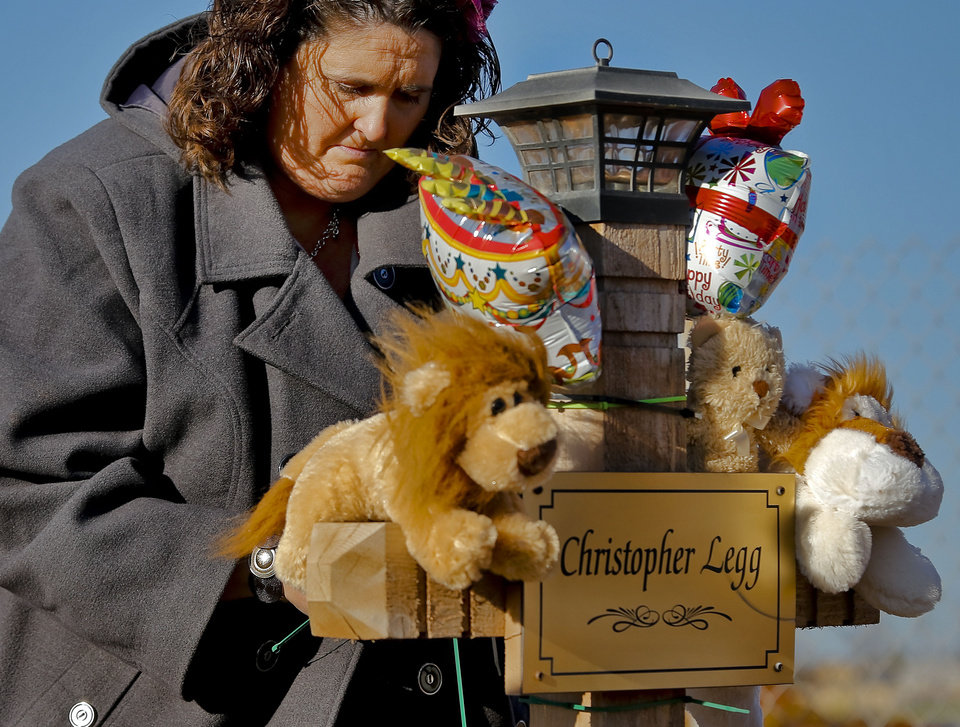 Photo - Danni Legg lowers her head while next to her son's, Christopher, wooden cross that stands outside the Plaza Towers Elementary School during a balloon release to mark what would have been Christopher's tenth birthday in Moore, Okla. on Thursday, Jan. 16, 2014. Christopher was killed along with six others when the May 20th tornado hit the school. Parents of those killed have been notified that the crosses will need to be removed for further rebuilding of the school. Photo by Chris Landsberger, The Oklahoman