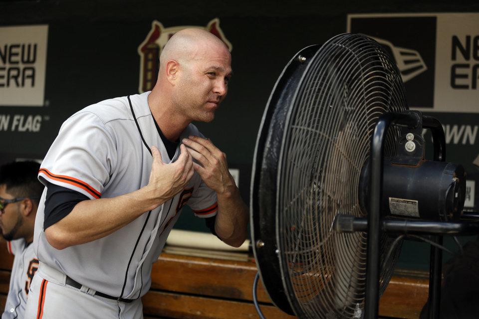Photo - San Francisco Giants starting pitcher Tim Hudson cools off in the dugout after working the fifth inning of a baseball game against the St. Louis Cardinals, Sunday, June 1, 2014, in St. Louis. (AP Photo/Jeff Roberson)