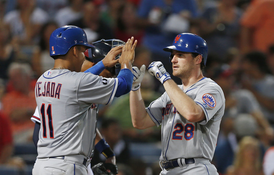 Photo - New York Mets second baseman Daniel Murphy (28) celebrates with New York Mets shortstop Ruben Tejada (11) after hitting a home run in the fifth inning of a baseball game against the Atlanta Braves in Atlanta, Tuesday, July 1, 2014.  (AP Photo/John Bazemore)