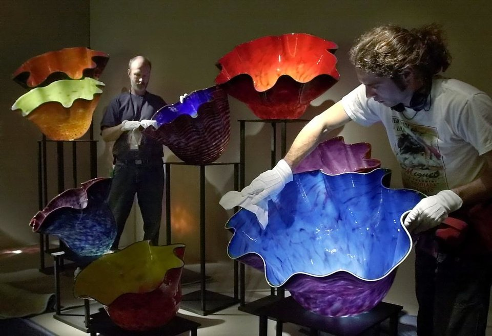 Photo - Jim Meeks, left, and Ernesto Sanchez dust and clean colorful glass pieces in the Dale Chihuly exhibit in the new Oklahoma City Museum of Art March 7, 2002. The Oklahoma City Museum of Art converted the old Centre Theater into its current downtown home, and in March 2002, the Oklahoma City Museum of Art opened its Donald W. Reynolds Visual Arts Center to long lines and great excitement. [The Oklahoman Archives]
