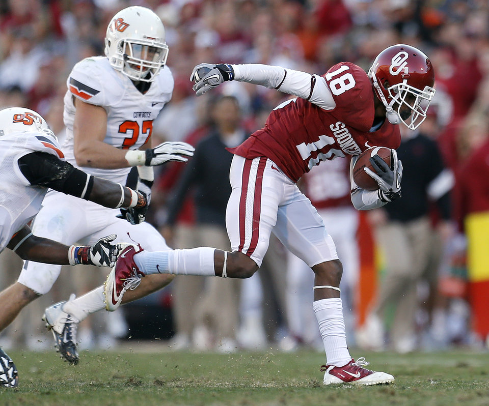 Photo - Oklahoma's Jalen Saunders (18) slips past Oklahoma State's Daytawion Lowe (8) and Lyndell Johnson (27) during the Bedlam college football game between the University of Oklahoma Sooners (OU) and the Oklahoma State University Cowboys (OSU) at Gaylord Family-Oklahoma Memorial Stadium in Norman, Okla., Saturday, Nov. 24, 2012. OU won 51-48 in overtime. Photo by Sarah Phipps, The Oklahoman