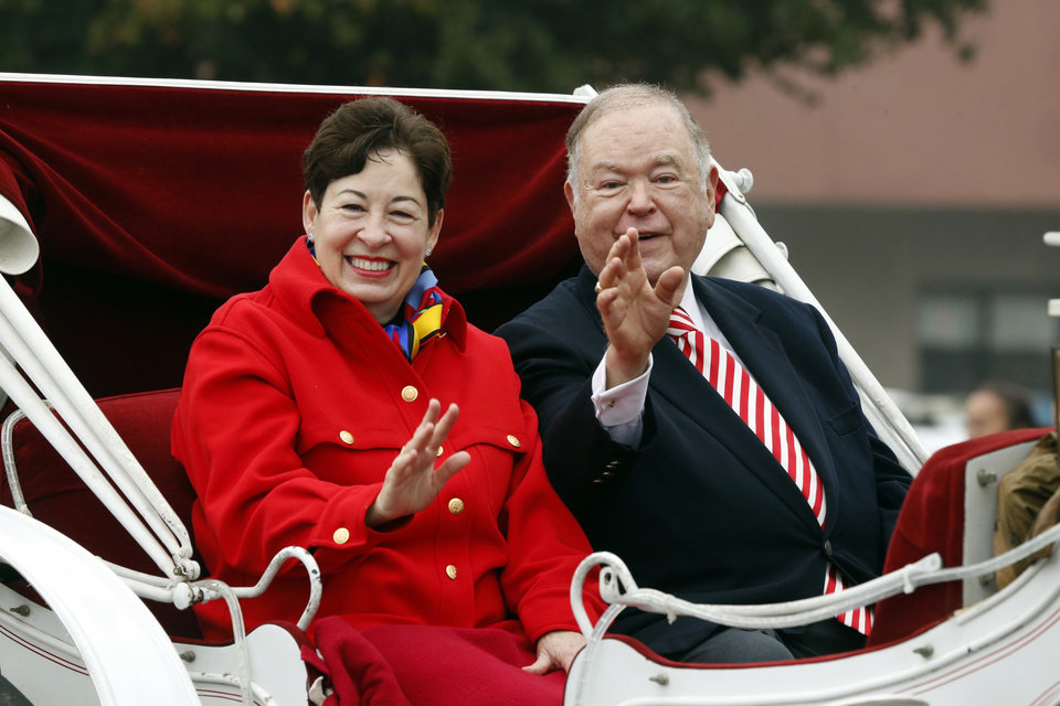 Photo - Molly Shi Boren and husband University of Oklahoma President David Boren ride in a carriage during the annual Norman Christmas Parade on Saturday, Dec. 13, 2014, in Norman , Okla.  Photo by Steve Sisney, The Oklahoman