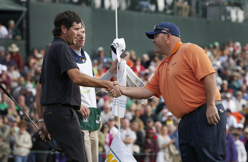 Photo - Kevin Stadler, right, winner of the Phoenix Open golf tournament, shakes hands with Bubba Watson on the 18th green after the final round Sunday, Feb. 2, 2014, in Scottsdale, Ariz. (AP Photo/Ross D. Franklin)