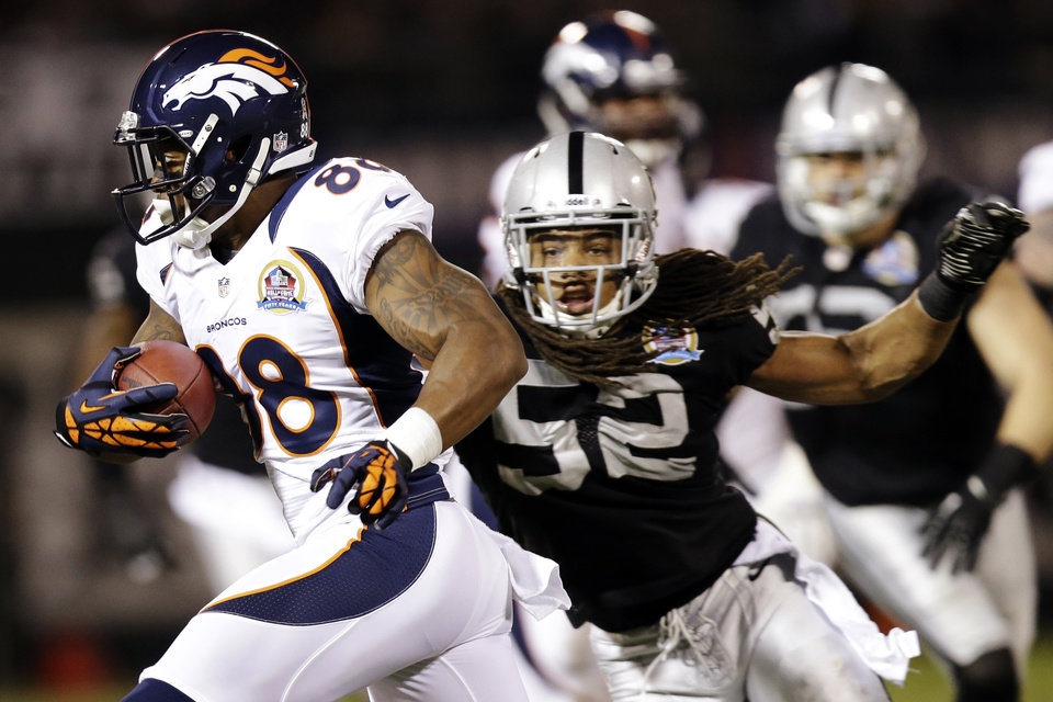 Denver Broncos wide receiver Demaryius Thomas (88) runs with the ball as Oakland Raiders outside linebacker Philip Wheeler, right, gives chase during the second quarter of an NFL football game in Oakland, Calif., Thursday, Dec. 6, 2012. (AP Photo/Marcio Jose Sanchez)