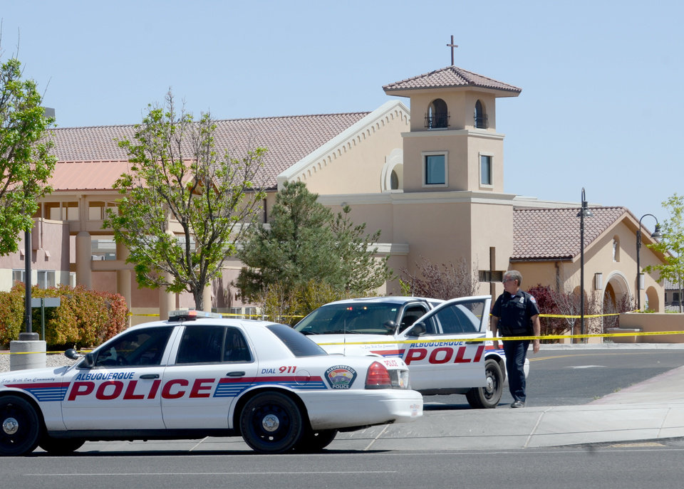 Photo - An Albuquerque Police officer walks behind the tape at St. Jude Thaddeus Catholic Church, Sunday April 28, 2013, in Albuquerque, N.M., the scene of a multiple stabbing at the conclusion of morning services. Police say a 24-year-old man stabbed four people at a Catholic church in Albuquerque as a Sunday mass was nearing its end. Police spokesman Robert Gibbs says Lawrence Capener jumped over several pews at church around noon Sunday and walked up to the choir area where he began his attack. (AP Photo/Albuquerque Journal, Dean Hanson)