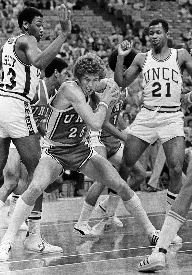 Photo - FILE - In this March 28, 1977 file photo, University of Nevada, Las Vegas' Glen Gondrezick, center, fights for the ball as  UNC-Charlotte teammates Lew Massey, left, and Chad Kinch, right, move in during first period of and NCAA college basketball game  in Atlanta. Gondrezick, who later played for the New York Knicks and Denver Nuggets before turning to broadcasting, died  Monday, April 27, 2009 at St. Rose Hospital in Henderson, Nev., after complications from a heart transplant last September, school officials and close friend Bobby Gleason said. He was 53.  (AP Photo/File) ORG XMIT: NY153