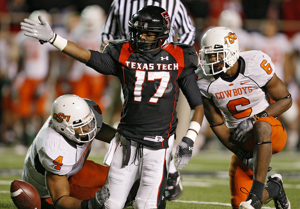 Photo - Texas Tech's Detron Lewis (17) signals for a first down after being brought down by Oklahoma State's Patrick Lavine (4) and Ricky Price (6) during the second half of the college football game between the Oklahoma State University Cowboys (OSU) and the Texas Tech Red Raiders at Jones AT&T Stadium on Saturday, Nov. 8, 2008, in Lubbock, Tex.  BY CHRIS LANDSBERGER/THE OKLAHOMAN  ORG XMIT: KOD