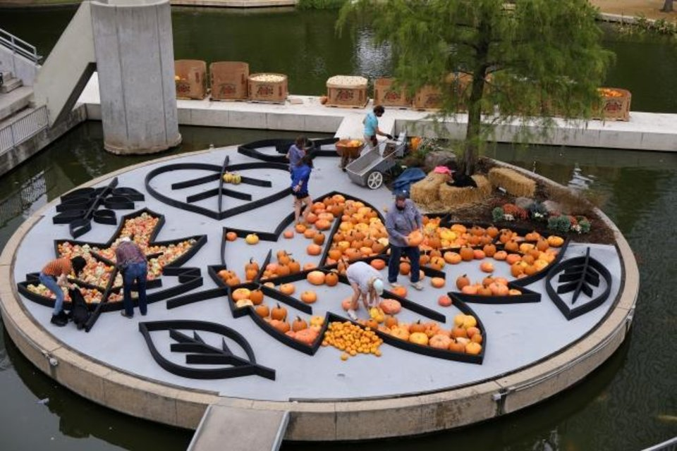 Photo -  Local artist Nick Bayer gets help building a giant pumpkin mural Oct. 9 on the Water Stage for the Myriad Botanical Gardens' Great Pumpkin Patch. [Doug Hoke/The Oklahoman]