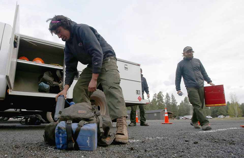 Photo - Firefighters gear up before going out to fight the Slide Fire on Friday, May 23, 2014, in Flagstaff, Ariz.  The fire has burned approximately 7,500 acres and is five percent contained. (AP Photo/Ross D. Franklin)