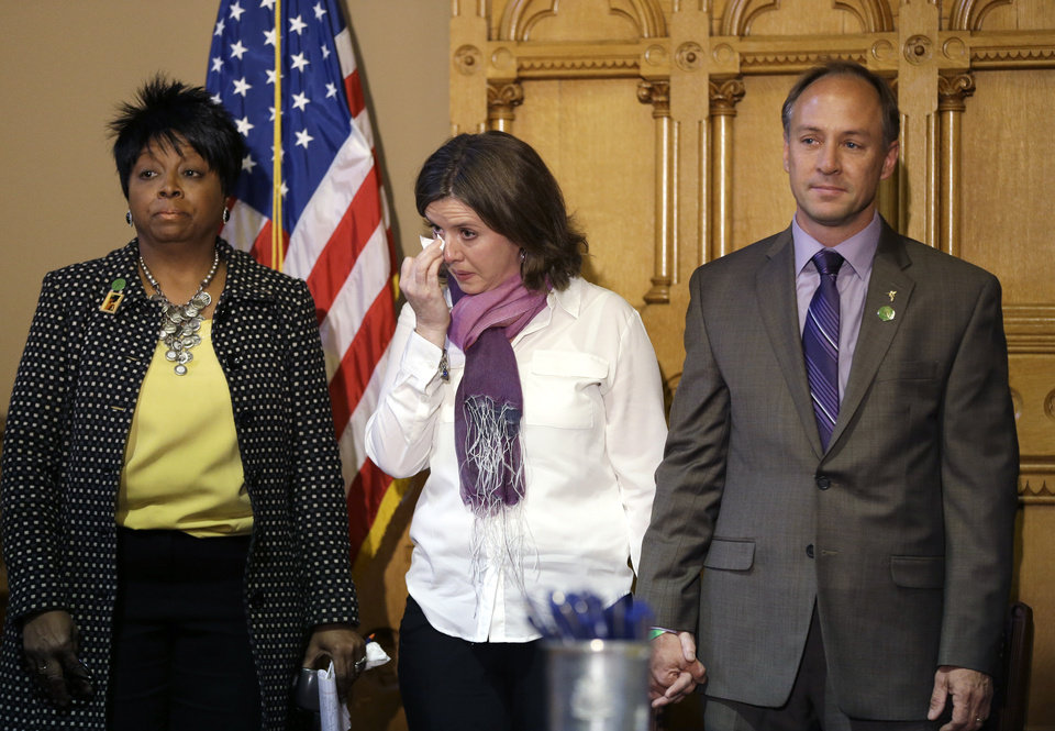 Photo - CORRECTS FIRST NAME OF FATHER TO MARK BARDEN INSTEAD OF DANIEL BARDEN - Jackie and Mark Barden, parents of Sandy Hook shooting victim Daniel Barden, center and right respectively, react while holding hands and standing next to Deborah Davis, left, who lost her son to gun violence in 2010, during a legislation signing ceremony at the Capitol in Hartford, Conn., Thursday, April 4, 2013. The legislation signed by Conn. Gov. Dannel P. Malloy brings into law new restrictions on weapons and large capacity ammunition magazines, a response to last year's deadly school shooting in Newtown. (AP Photo/Steven Senne)