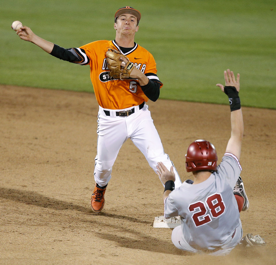 Photo - OSU's Donnie Walton throws over OU's Mac James for a double play in the 10th inning of a Bedlam baseball game between Oklahoma State University and the University of Oklahoma in Stillwater, Tuesday, April 15, 2014. Photo by Bryan Terry, The Oklahoman