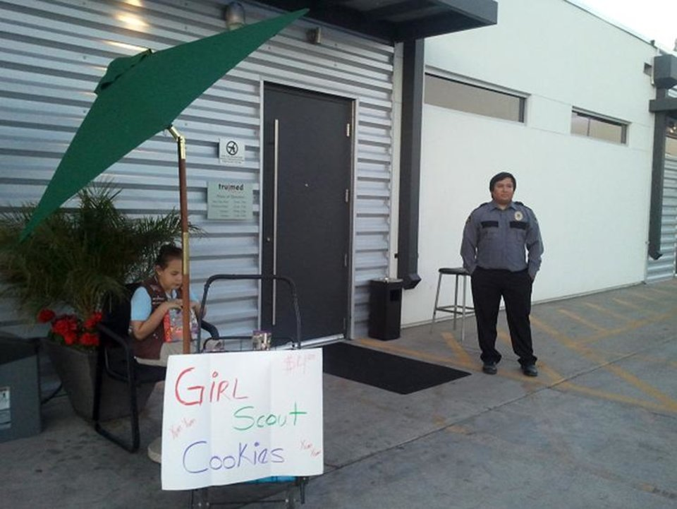 Photo - Lexi Menees, 8, sells Girl Scout Cookies while sitting outside Trumed Dispensary, which sells medical marijuana for licensed patients, in Phoenix on Friday, Feb. 21, 2014.  Girl Scouts seem to be foregoing the usual supermarket stops for selling their beloved cookies.  A few days after a teenager sold dozens of cookie boxes outside a San Francisco pot dispensary,  Menees, 8,  will return to Trumed Dispensary in Phoenix on Saturday for the same purpose.  The girl's mother, Heidi Carney, got the idea after hearing about what happened in San Francisco.  Susan de Queljoe, a spokeswoman for the Girl Scouts, Arizona Cactus-Pine Council, says this is not something the organization would encourage but that it's up to the parents. (AP Photo/Terry Tang)