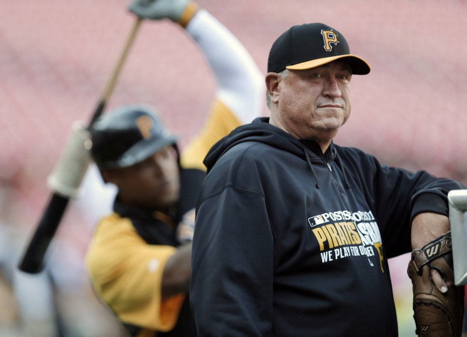 Photo - FILE - In this Oct. 9, 2013, file photo, Pittsburgh Pirates manager Clint Hurdle, right, watches his team warm up for Game 5 of a NL baseball division series between the Pirates and the St. Louis Cardinals in St. Louis. Hurdle has won the NL Manager of the Year award after guiding the Pirates to the playoffs in their first winning season since 1992. (AP Photo/Charlie Riedel, File)