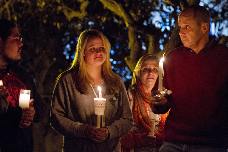 Photo - Kerin Sovern, center, who is from Sandy Hook, Connecticut, but now lives in San Diego, attends a candlelight vigil honoring victims of the Sandy Hook Elementary School in Connecticut at Balboa Park Thursday Dec. 20, 2012 with her parents Maureen and Michael Sovern who are visiting her from Sandy Hook. (AP Photo/U-T San Diego, Bill Wechter