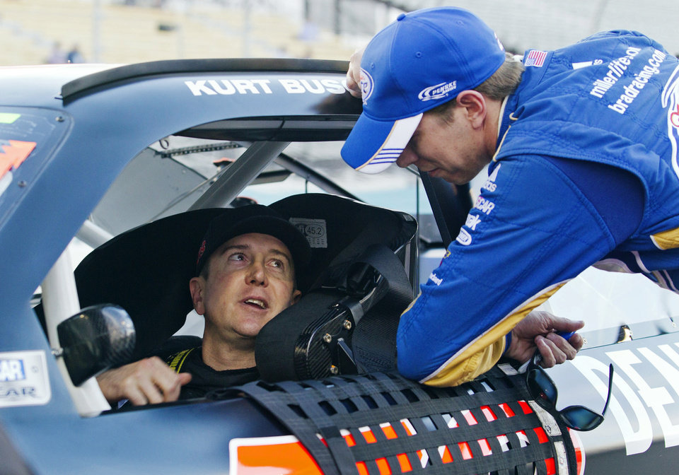 Photo -   Kurt Busch, left, talks with Brad Keselowski, right, during qualifying for the NASCAR Sprint Cup Series auto race, Friday, Nov. 9, 2012, at Phoenix International Raceway in Avondale, Ariz. (AP Photo/Paul Connors)
