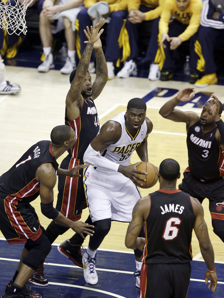 Indiana Pacers' Roy Hibbert (55) goes to the basket against Miami Heat's Chris Bosh (1) and Udonis Haslem (40) during the first half of Game 3 of the NBA Eastern Conference basketball finals in Indianapolis, Sunday, May 26, 2013. (AP Photo/Michael Conroy)