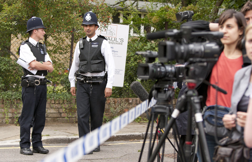 Photo - Policemen stand next to a police cordon where media are gathered, near to the home of British singer Amy Winehouse in Camden Square, following her death, Saturday, July 23, 2011.  The cause of death was not immediately known, and London Ambulance Services said Winehouse had died before the two ambulance crews arrived at the scene.(AP Photo/Joel Ryan) ORG XMIT: LENT107