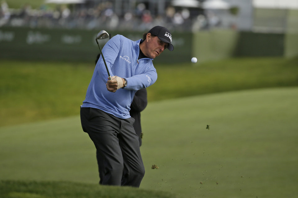Photo -  Phil Mickelson chips the ball up to the sixth green of the Pebble Beach Golf Links during the third round of the AT&T Pebble Beach National Pro-Am golf tournament on Saturday. [AP Photo/Eric Risberg]