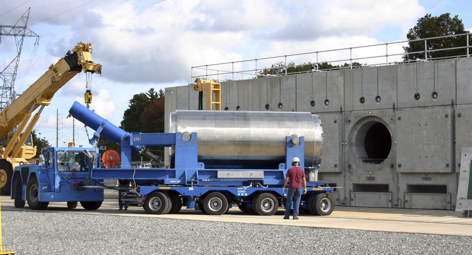 Photo - In this Oct. 14, 2010 photo released by Dominion Resources, a trailer holding a spent fuel storage container is maneuvered into position for offloading into a horizontal storage module at the Millstone Power Station in Waterford, Conn. With the collapse of a proposal for nuclear waste storage at Nevada's Yucca Mountain, Millstone and other plants across the country are building or expanding on-site storage for waste.(AP Photo/Dominion Resources)