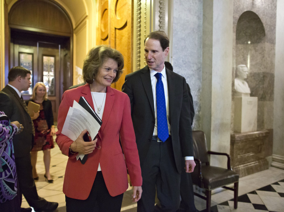 Photo - Sen. Lisa Murkowski, R-Alaska, left, and Sen. Ron Wyden, D-Ore., right, leave the Senate floor after voting on legislation to collect sales tax on Internet purchases, on Capitol Hill in Washington, Monday, May 6, 2013.  (AP Photo/J. Scott Applewhite)
