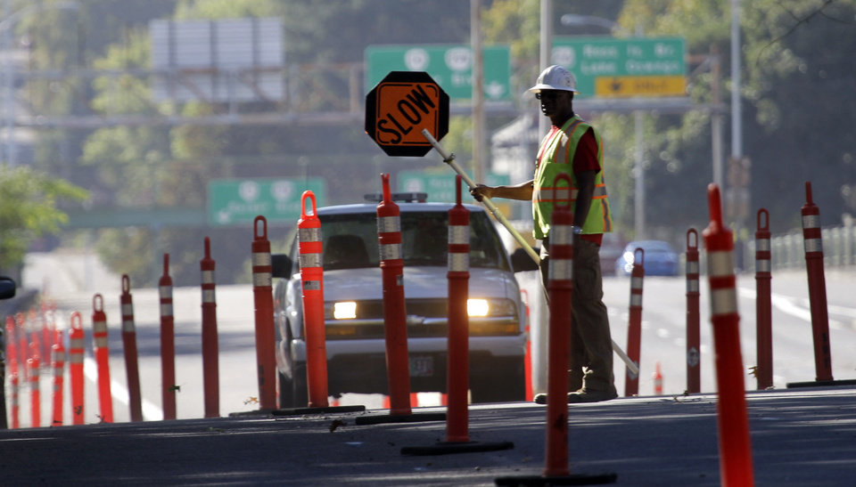A worker directs traffic for street construction Friday in Portland, Ore. AP Photo