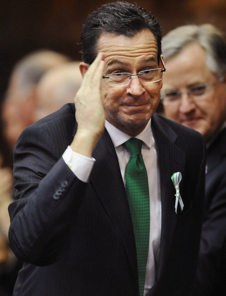 Photo - Connecticut Gov. Dannel P. Malloy, salutes as he arrives to speak to the House and the Senate in his State of the State address at the Capitol in Hartford, Conn., Wednesday, Jan. 9, 2013. Gun control, mental health care and school safety are expected to be major topics in the new session. Legislators also must grapple with a projected deficit of about $1.2 billion. (AP Photo/Jessica Hill)